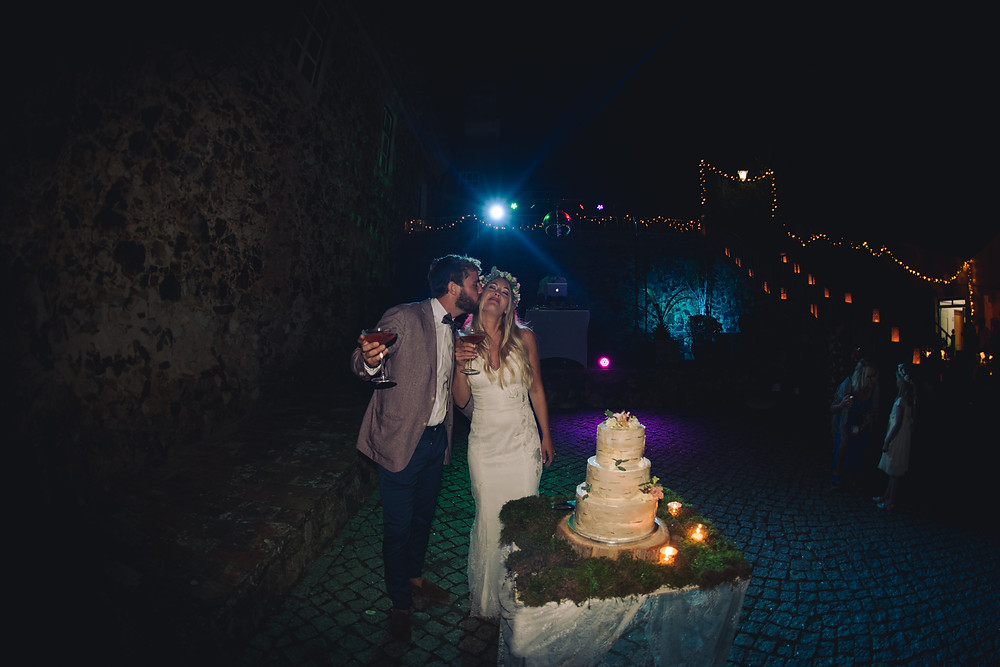 Bride and groom kissing in front of their wedding cake in Portugal