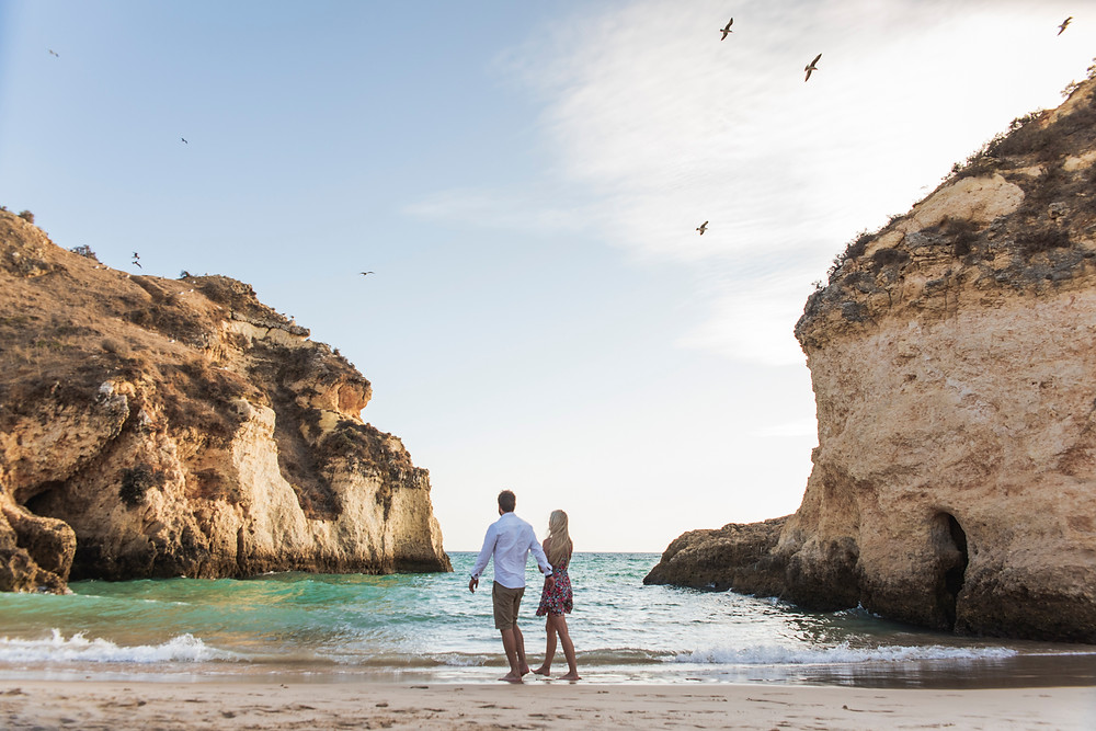 Engaged couple walking along the three brothers beach in Alvor, Portugal