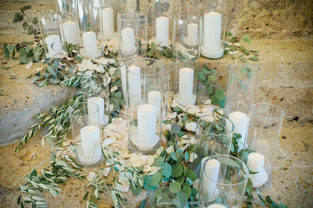 Church candles in glass vases surrounded with leafs on stone steps