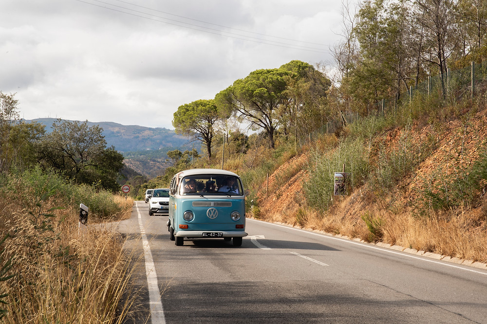 Pale blue VW camper van driving in the countryside of Monchique, Portugal.