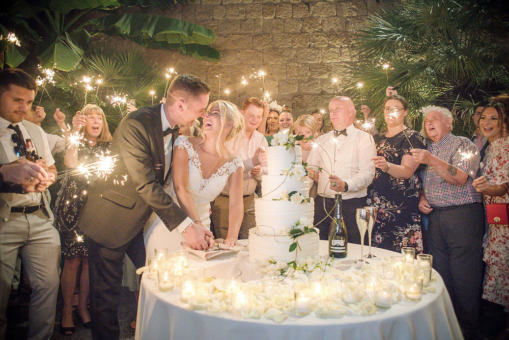 married-couple-cutting-a-wedding-cake-surrounded-by-wedding-guests-holding-sparklers