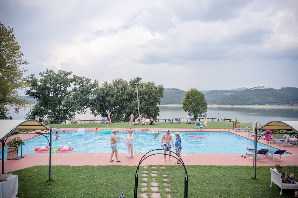 Wedding guests enjoying the pool party, lake in the background