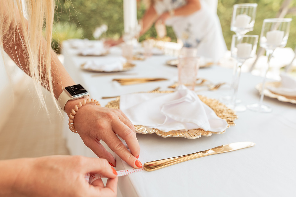 ARW Event planner measuring the distance of a gold knife to the edge of the table for a Portugal wedding
