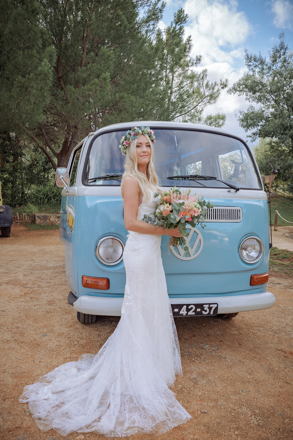 Beautiful wedding bride standing in front of a VW Camper van holding a wedding bouquet of protea flowers