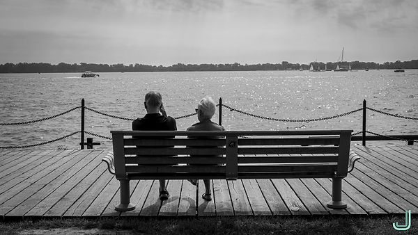 A couple seated on a park bench looking at the lake