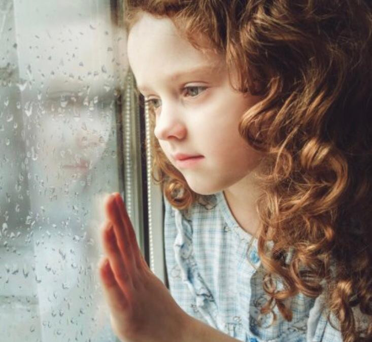 Little girl staring outside the window with rain