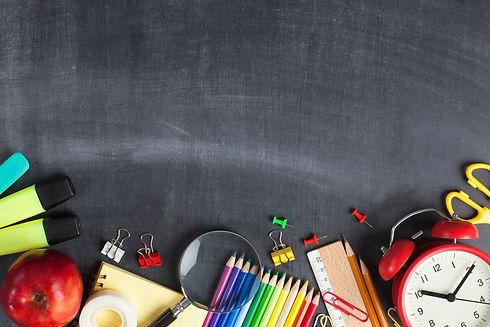 School supplies on black board backgroun