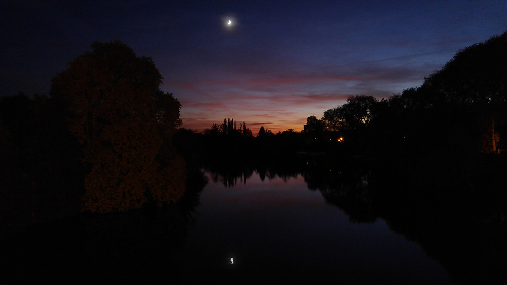 The moon and the last rays of the sunset reflected upon the Vienne River at Confolens, France.