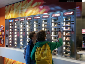 Two pre-teen boys standing in front of a FEBO automat wall in the Rotterdam Centraal train station. One boy is putting a coin in buy some food. Photo by @REGANLAND.