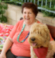 Female resident sitting with assistance dog.
