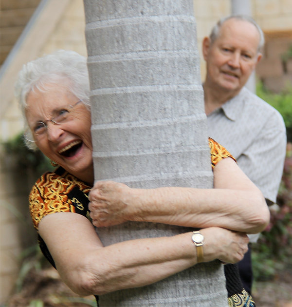 Female resident laughing while hugging tree.