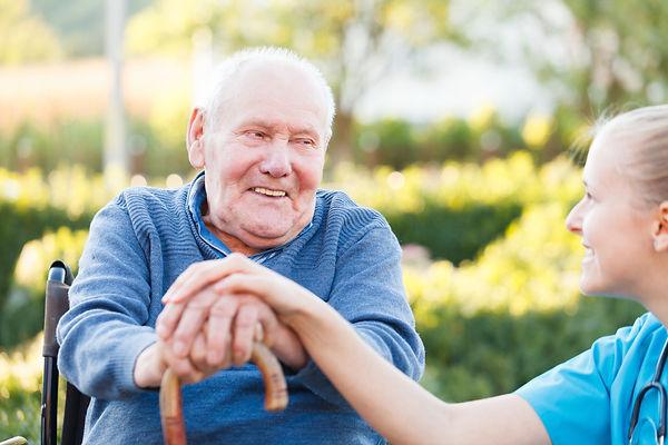 Aged care worker with elderly gentleman in wheelchair