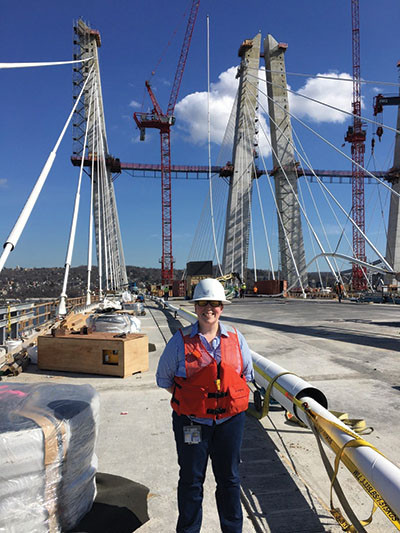 Wearing a hardhat and a safety vest, Hannah Carmical poses onsite at the Governor Mario M. Cuomo Bridge project in New York.