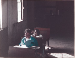 Two young girls sitting at the desks a Hosanna