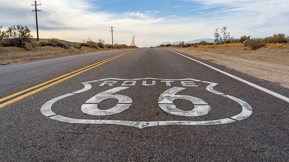 Route 66 sign painted on open road in California.
