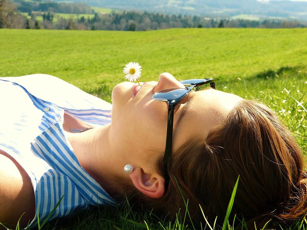 Woman in Sun, Woman lying in field, Woman in Nature, Sun Bathing, Green fields, blue sky, natural scene, outside, outdoor, flower, lying in the sun