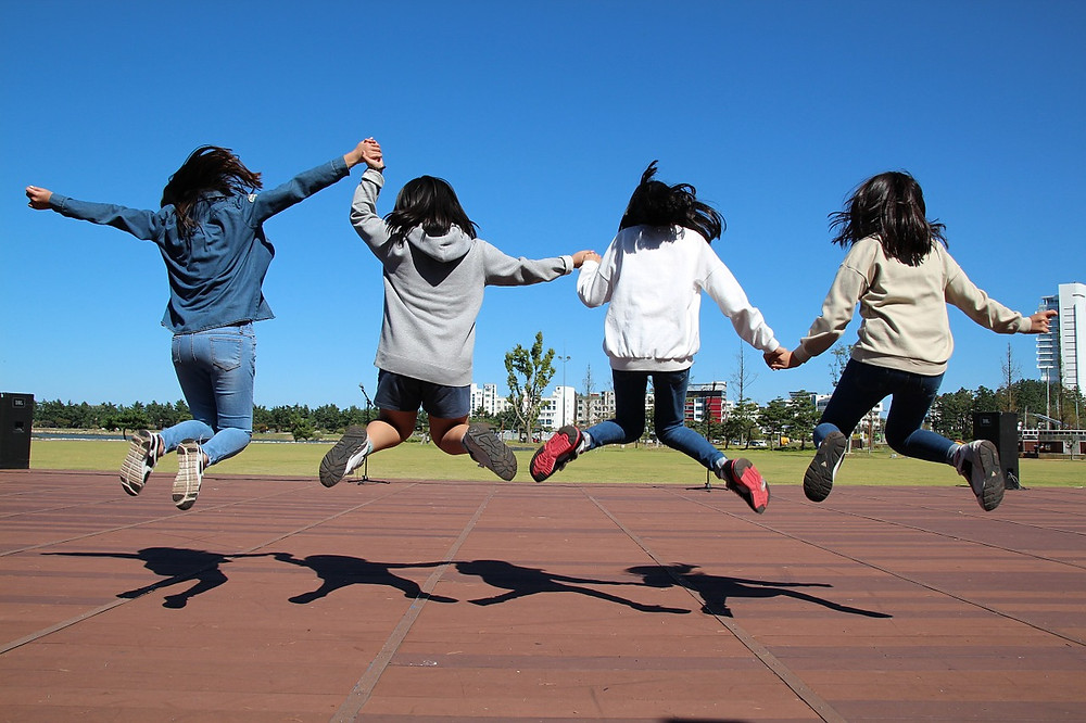 Young children, children, playing, joyful, playground, jumping, holding hands, sunny day, happy, youthful,