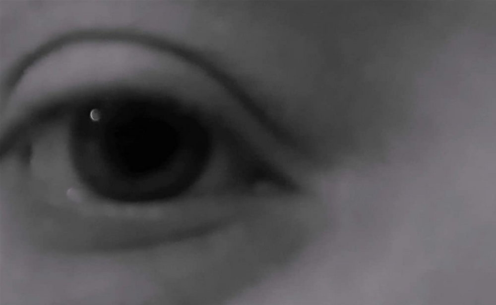 Still Image from Dying Alone showing closeup of eye.