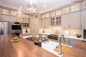 Beige and wood kitchen, stained kitchen island, farmhouse sink, stainless steel appliances, prep sink, gas range