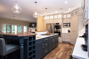 Beige and wood kitchen, dark stained kitchen island, farmhouse sink, stainless steel appliances, prep sink, gas range