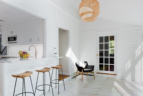Kitchen mudroom combination, wooden top barstools, kitchen peninsula, white countertop, detailed lighting fixtures