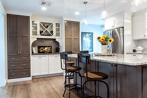 Tan and white kitchen, granite top island, swivel bar stools, built in custom cabinetry, built in wine cabinet, stainless steel appliances