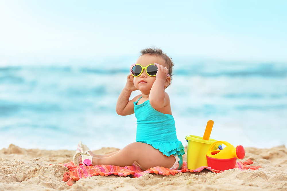 Baby in blue swimsuit sits on towel at the beach wears yellow sunglasses