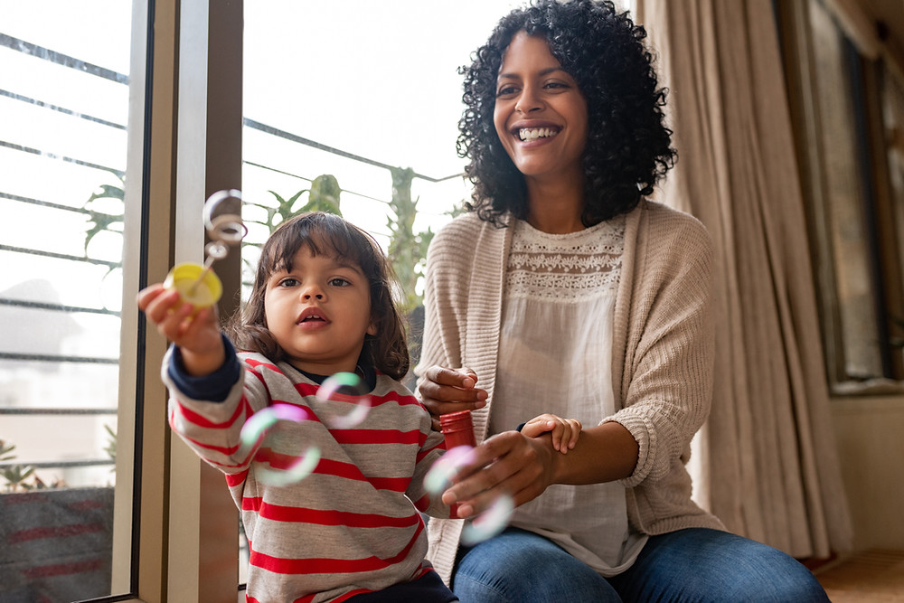 Toddler girl in red striped shirt tries to catch bubbles with bubble wand while sitting next to her mother who is smiling and wearing a white shirt with a pink cardigan.