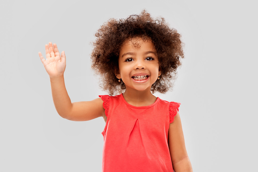 Young girl with brown curly hair smiles and waves