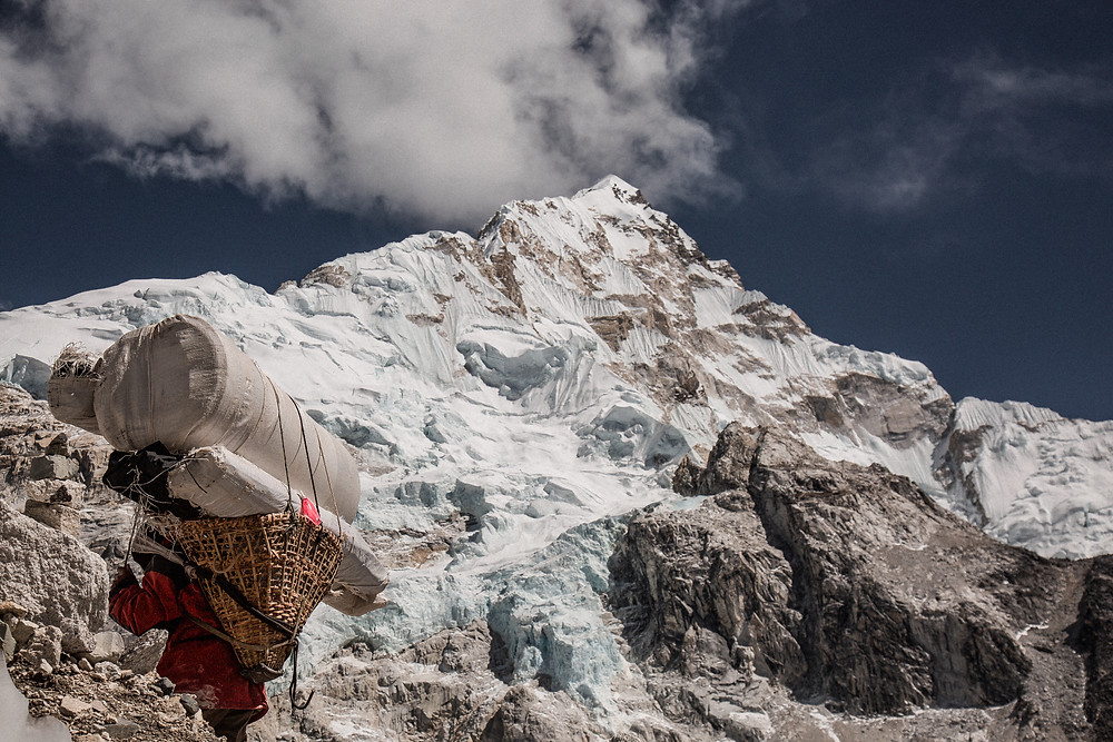 Sherpa cargando con muchos bultos mientras sube una montaña.