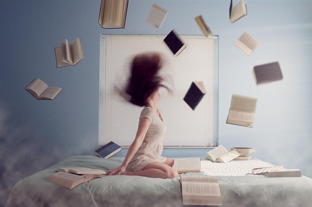 Mujer en la cama mientras caen libros del cielo.