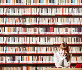 Ragazza che legge in biblioteca