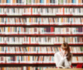 Mulher lê livro na biblioteca