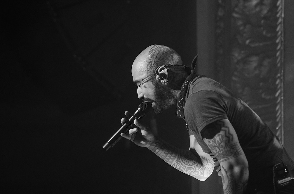 Nahko Bear singing into a mic with eyes closed looking calm. By music photographer Bret Stein.