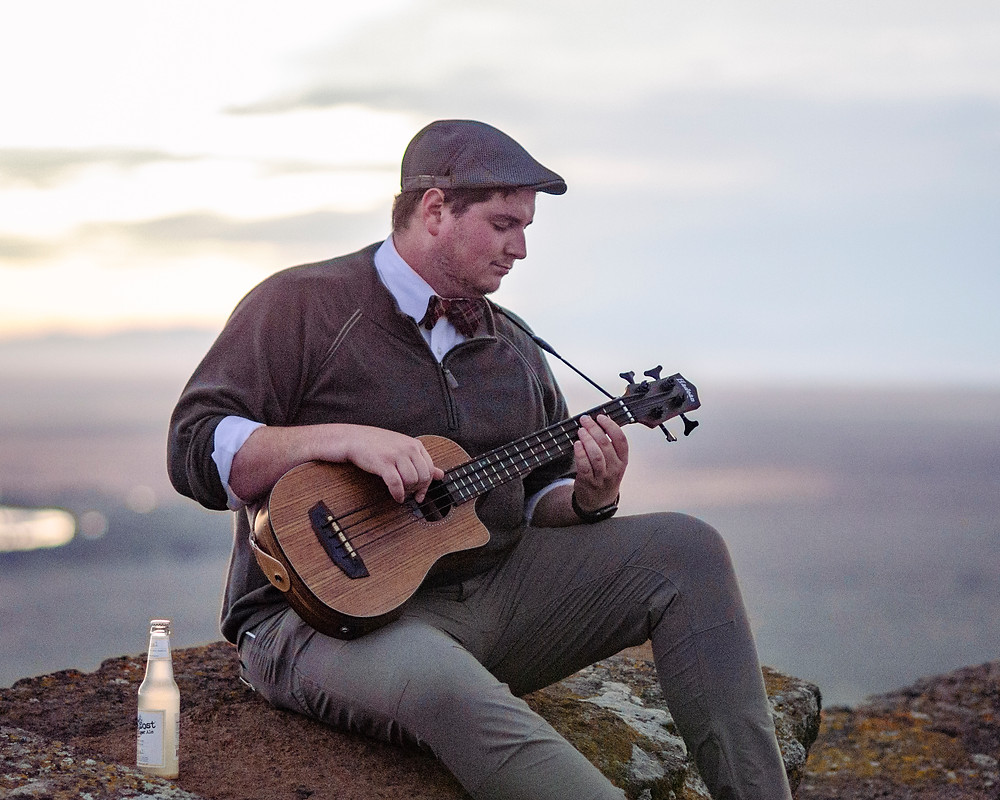 musician portrait of Ned Wilcox wearing a bow tie pleaying a ukulele on menan butte by music photographer Bret Stein
