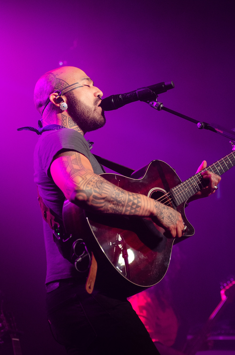Nahko Bear singing and playing guitar with a colorful background at the Spanish Ballroom. By music photographer Bret Stein.