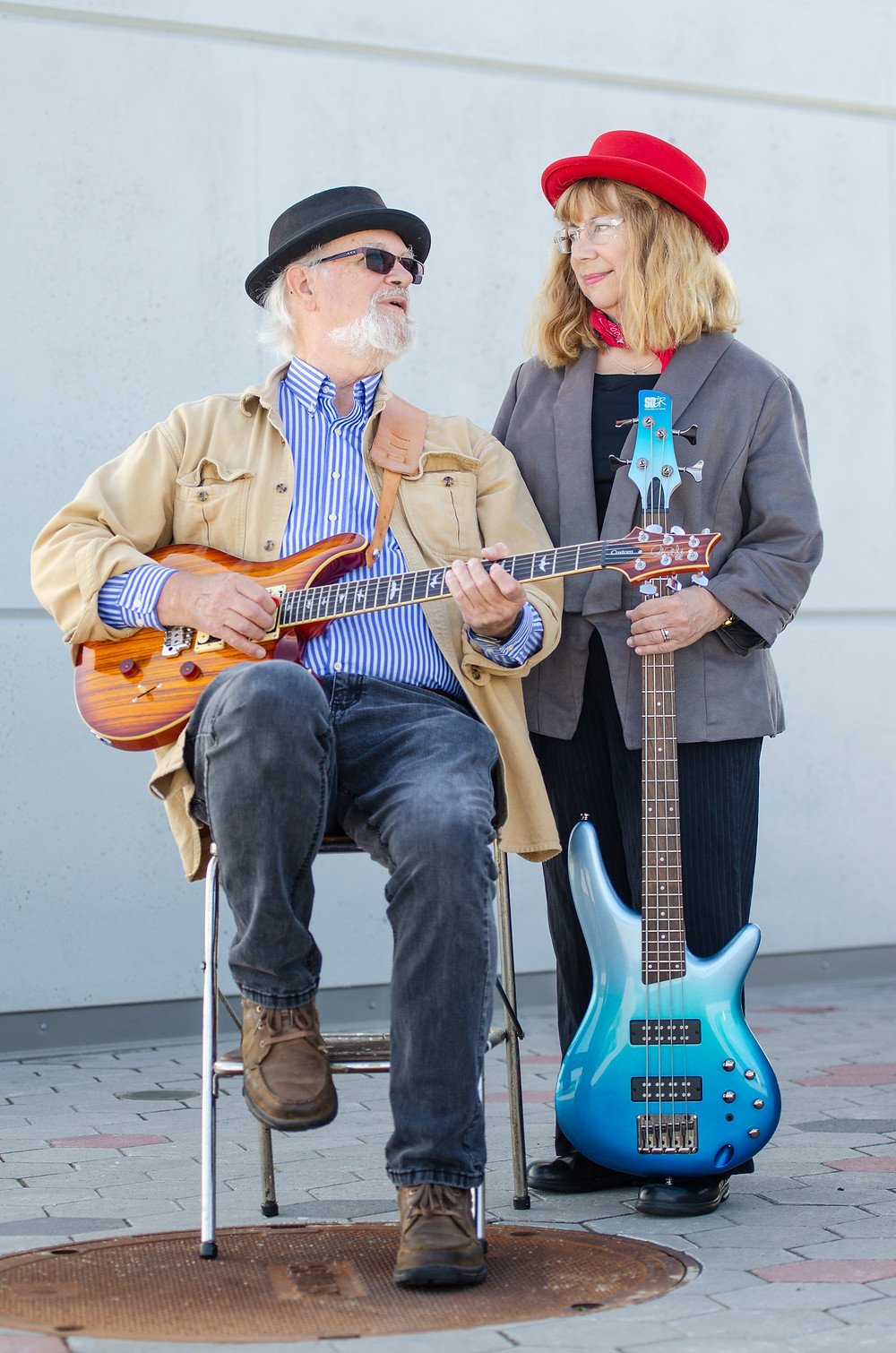 Portrait of music duo Steve and Krisit Nebel with guitars and cements background by Tacoma music photographer Bret Stein