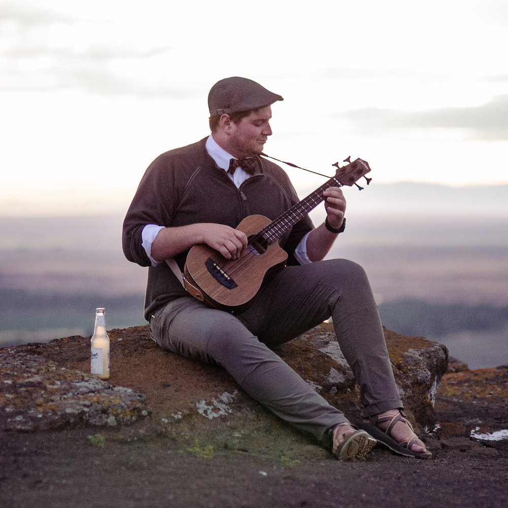 Musician Ned Wilcox plays bass ukulele at sunset on menan butte Idaho by music photographer Bret Stein
