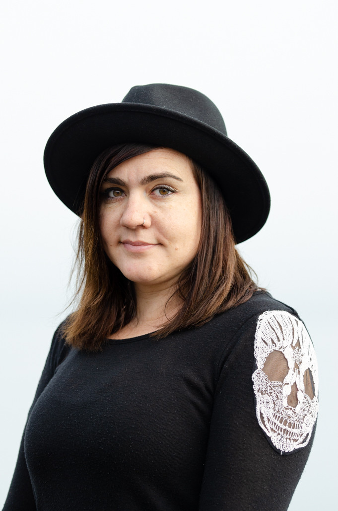 Musician Kristen Marlo wearing a black hat and smiling with fog background. Music portrait by music photographer Bret Stein