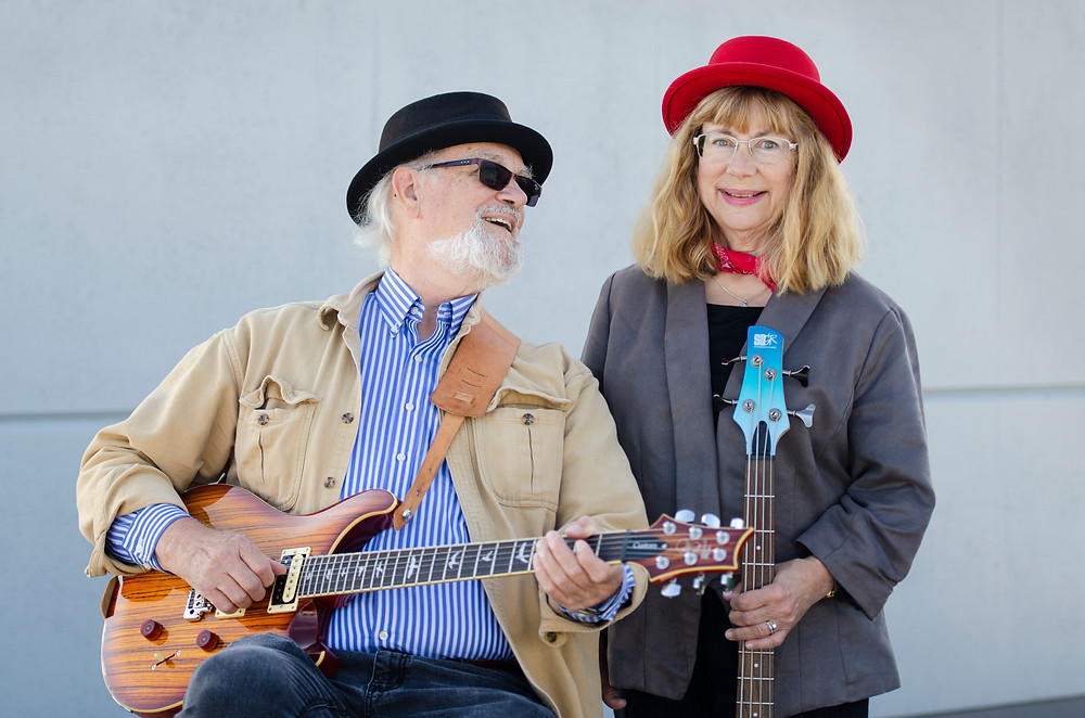 Portrait of music duo Steve and Krisit Nebel smiling with guitars and a cement background by Bret Stein