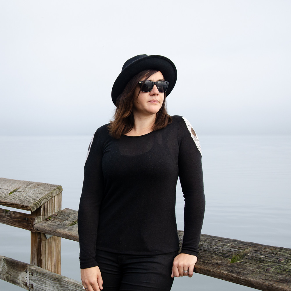 Musician Kristen Marlo on a pier with water and fog in the background. Music portrait by music photographer Bret Stein