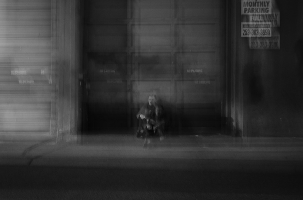 Intentionally blurry photo of Tacoma musician Trusty Sea Creature sitting in front of a garage by photographer Bret Stein