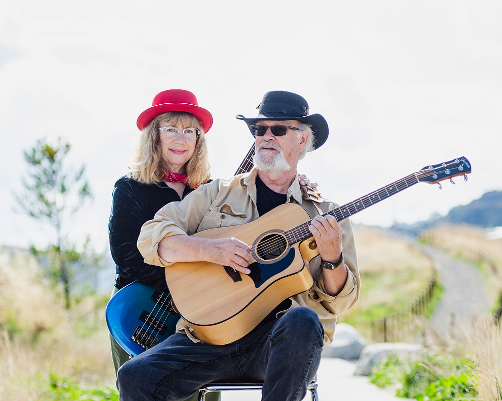 Portrait of music duo Steve and Krisit Nebel with grass background by Bret Stein at Dune Park Tacoma Washington