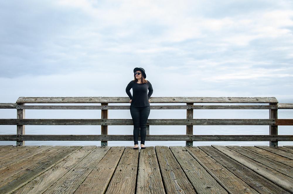 Musician Kristen Marlo standing on Les David Pier Tacoma. Music portrait by music photographer Bret Stein