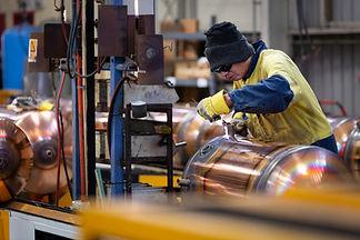 A Welder working on a hot water cylinder for Rheem NZ