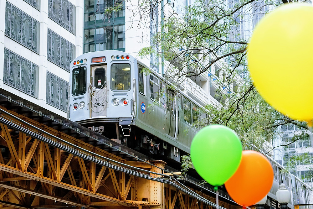 Balloons in front of an elevated train