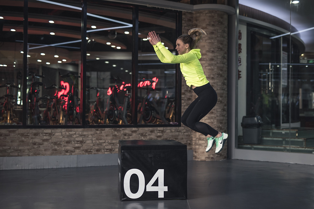A woman exercising with a large fitness block