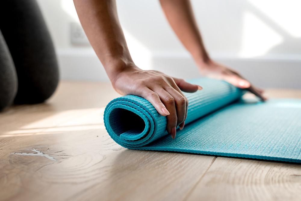 A woman unrolling an exercise mat
