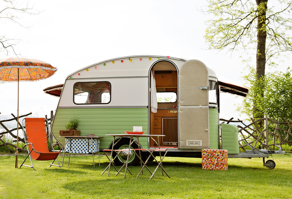 Retro white and pale green canned ham camping trailer with a table and chairs outside the door