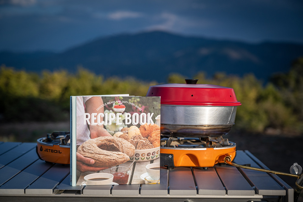 Omnia Stovetop Oven with cookbook on a table in the mountains